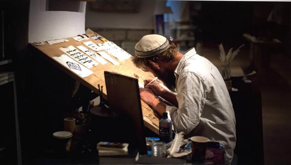 israeli scribe working on new art piece