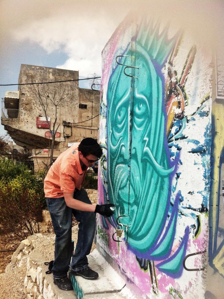 Israeli street artist spray painting electricity box