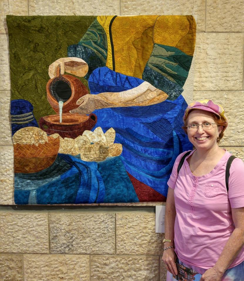 Israeli quiltmaker stands in front of her art piece depicting a woman pouring milk out of a jug