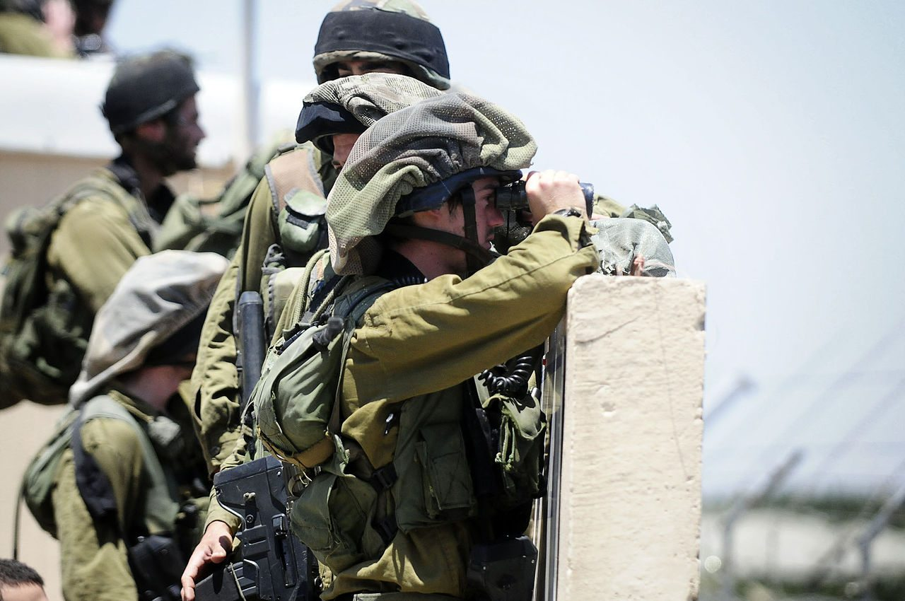 idf soldiers in training looking through their binoculars at the idf training base city during training