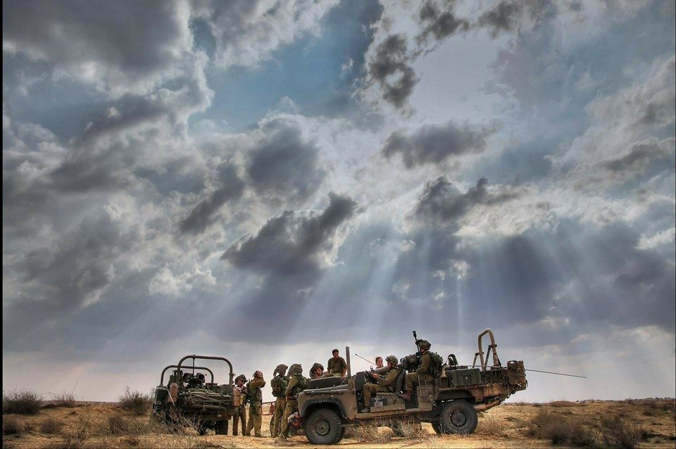 IDF soldiers in the field in military vehicles with beautiful cloudy sky