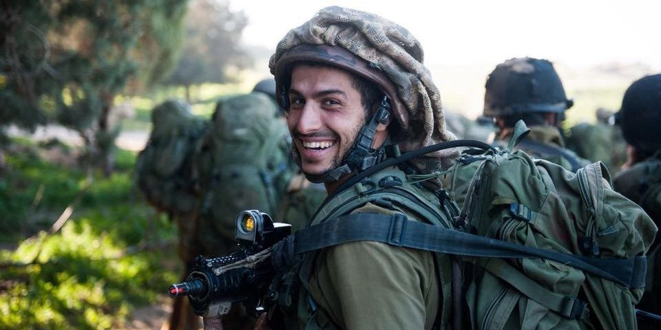 IDF soldier in full gear out in the field smiling