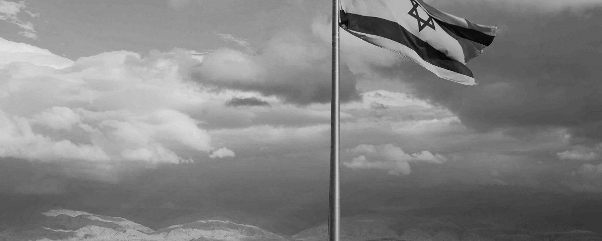 black and white Israeli flag against cloudy sky and mountain view