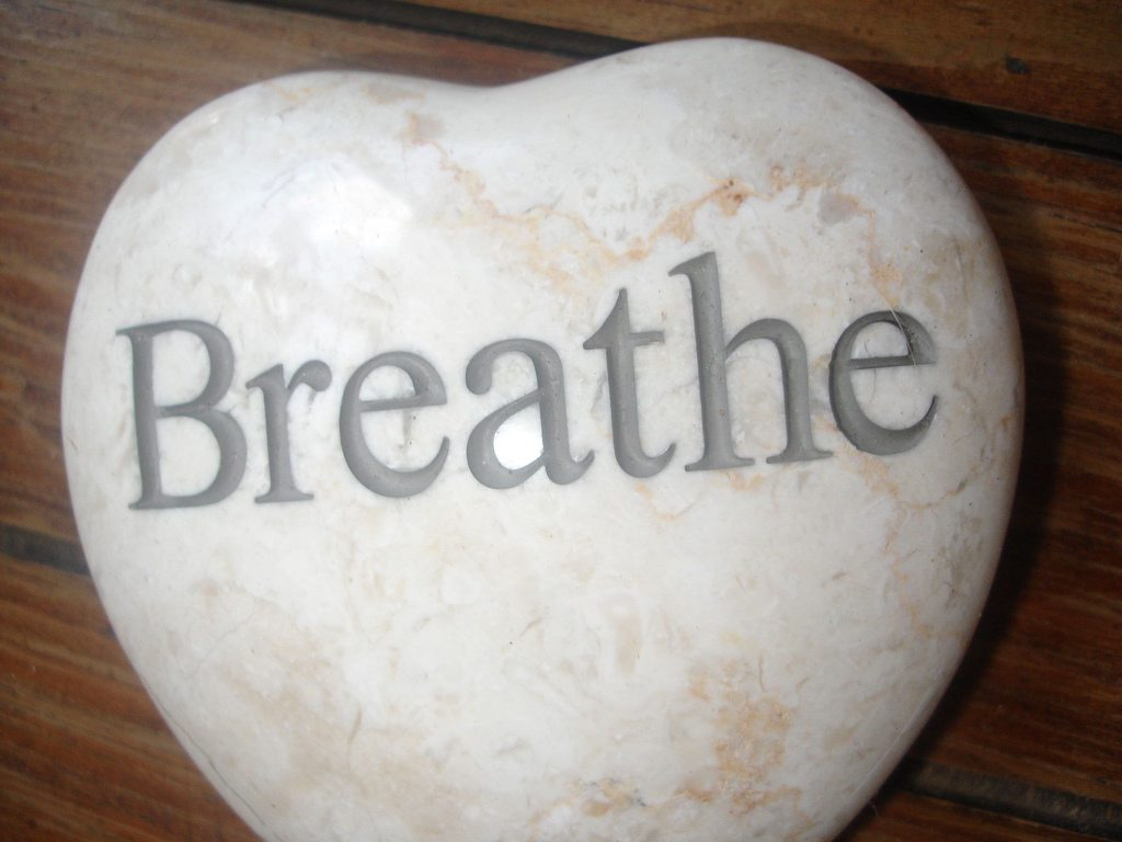 "Heart-shaped rock engraved with the word ""Breathe"""