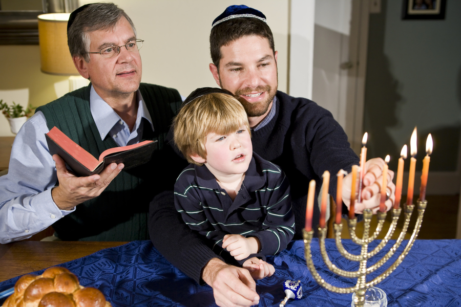torch relay on hanukkah. father son and grandfather lighting the menorah or rather hanukiyah on Janukkah