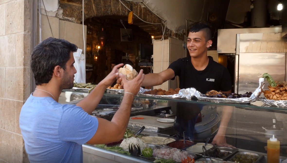 A guy buying falafel in a falafel stand in israel for culinary delight