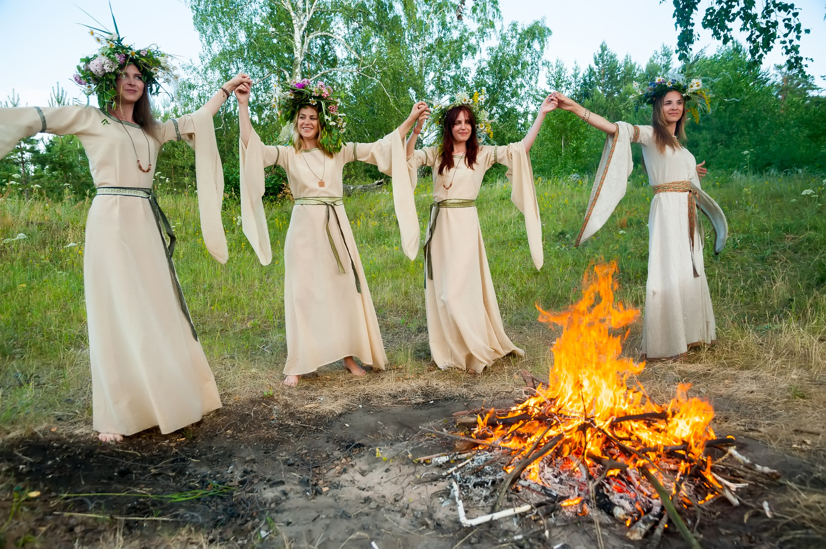 women dancing in white dresses in the forest around a bonfire like the women of tu bav who were dancing in the vineyard to look for a husband in tu bav