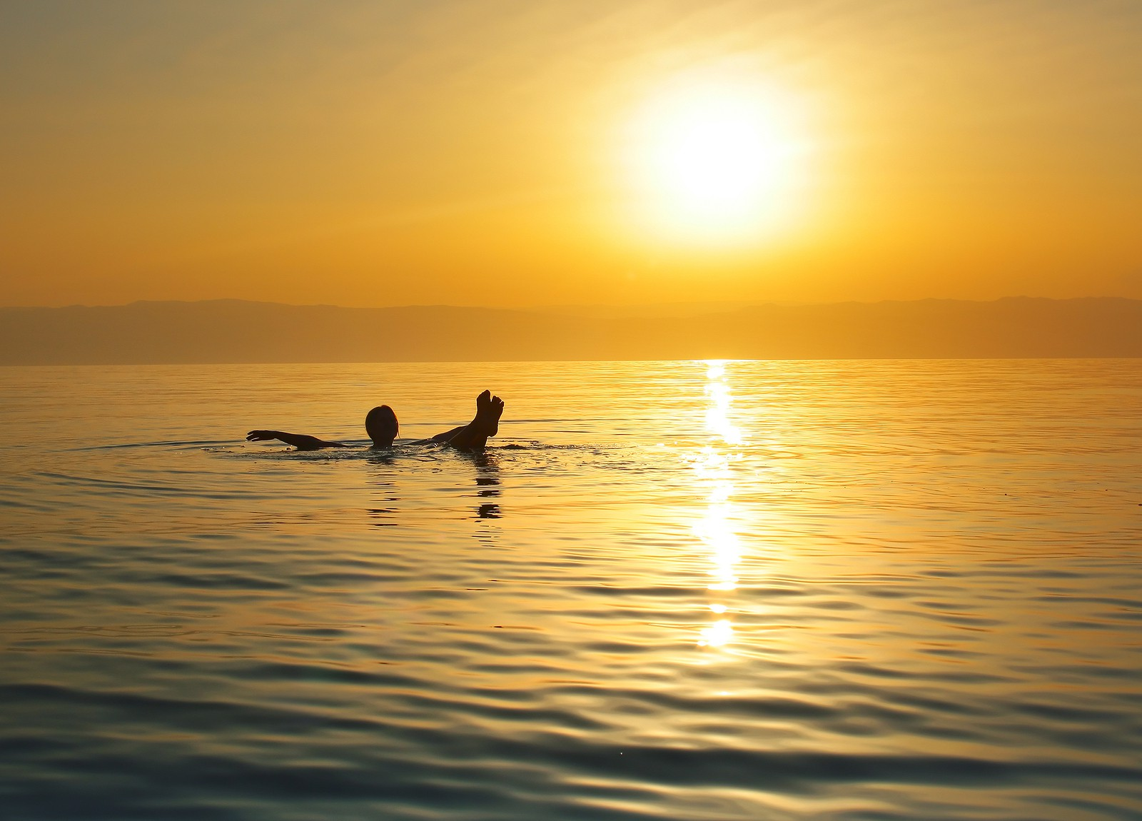 a person floating in the sea during sunset chilling and relaxing