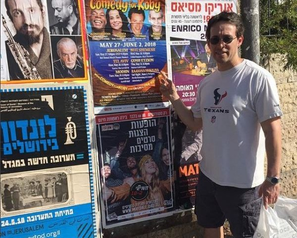 avi liberman pointing at a an ad for comedy for koby