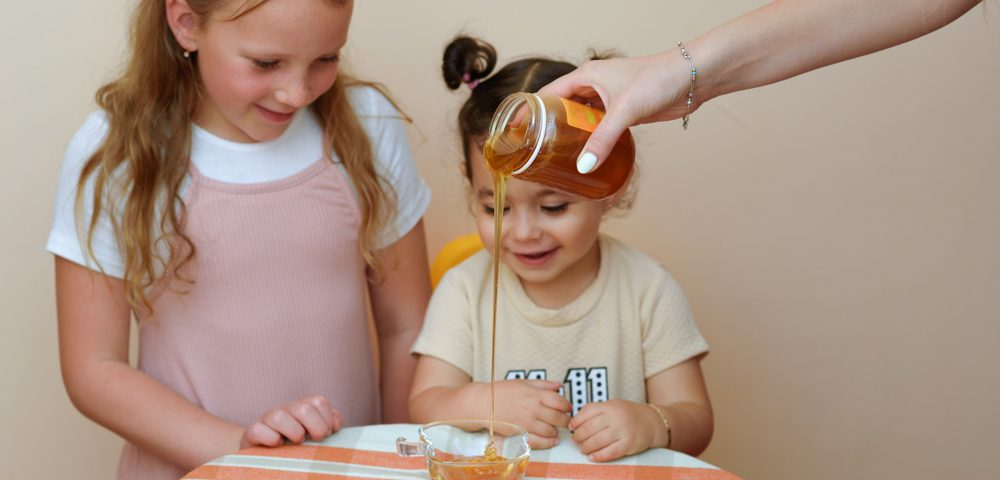 honey for a sweet new year with two kids smiling
