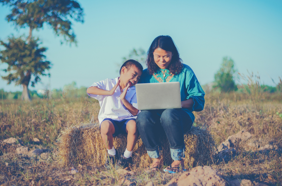 An Asian mom and son sitting outside at the countryside with a laptop showing that the mom could study at the university of the people while keeping her obligations to her family