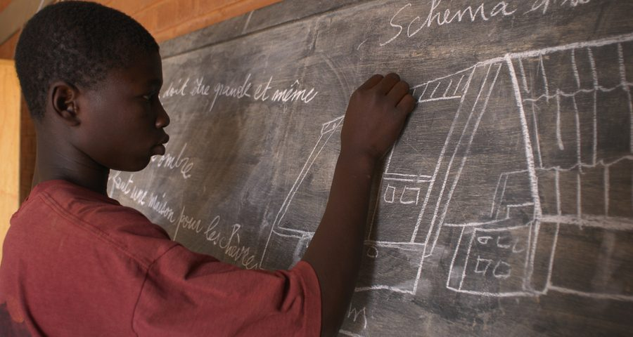 An African teenager solving a math question in a blackboard linked to university of the people