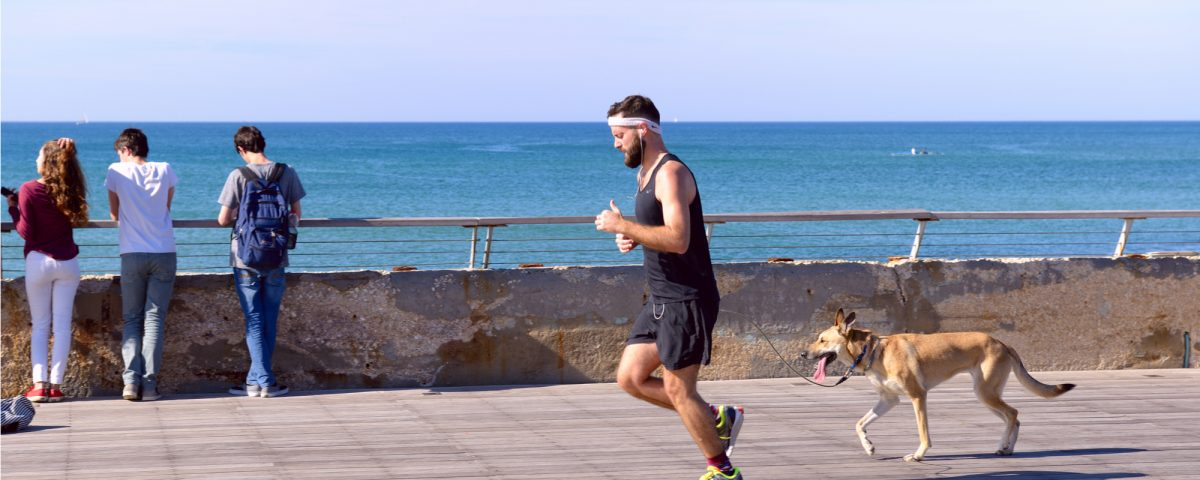 A guy running at the tayelet of tel aviv in israel with his dog and people are watching the view of the ocean in the background