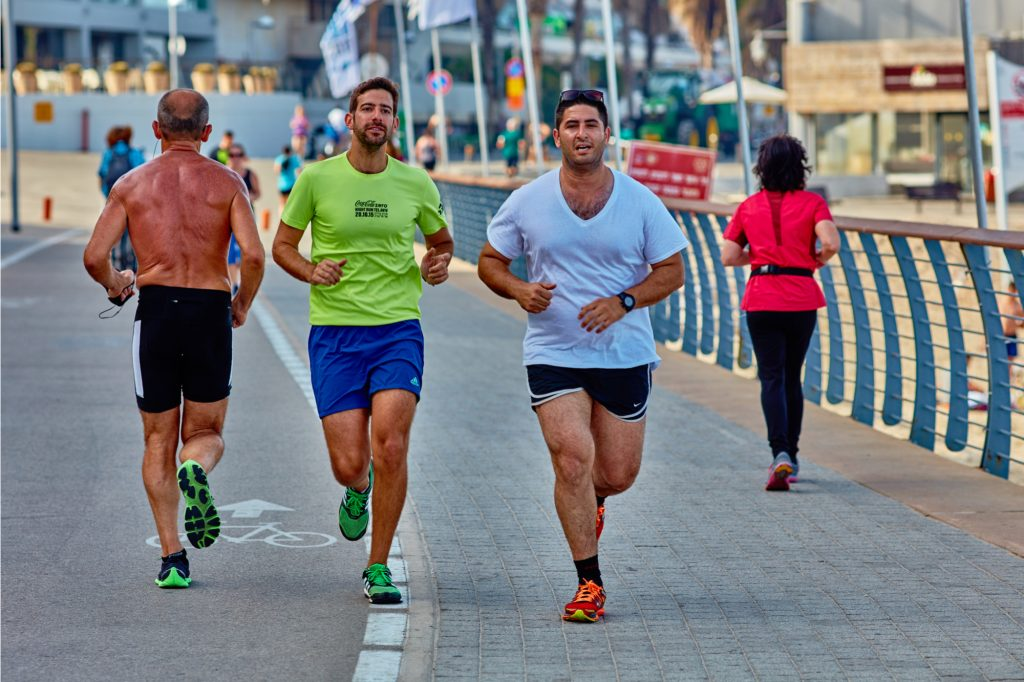 two guys running at the tel aviv promonade by the beach showing a post holiday workout