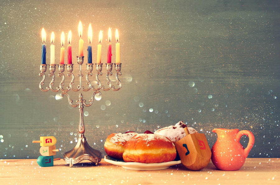 menora, doughnuts, dreidel, and a pitcher of oil all Hanukkah symbols