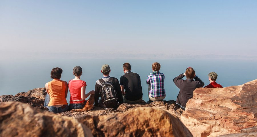 a group of travelers sitting by the view of the dead sea on the mountains