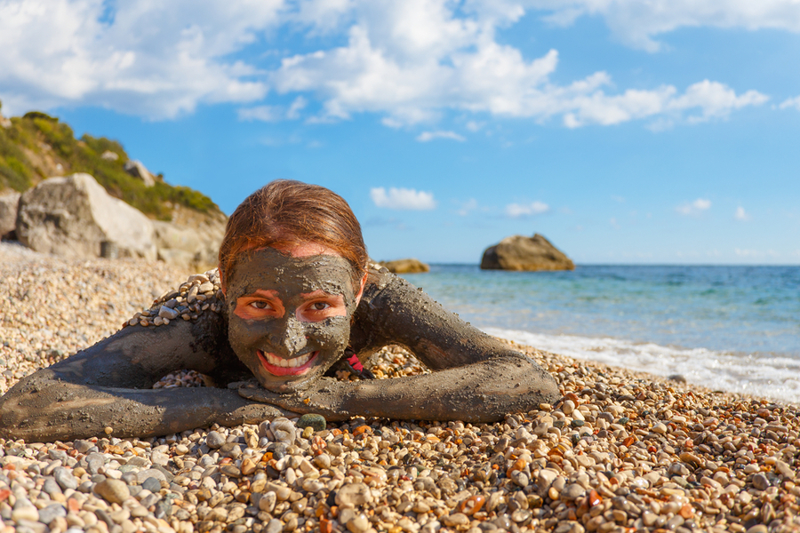girl smiling with dead sea mud on her face lying down on the beach face front to the camera - israel