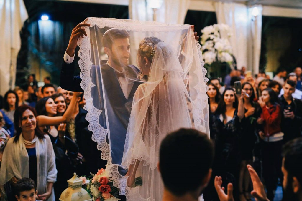 An Israeli groom covering his bride's head with her vail for the chupah