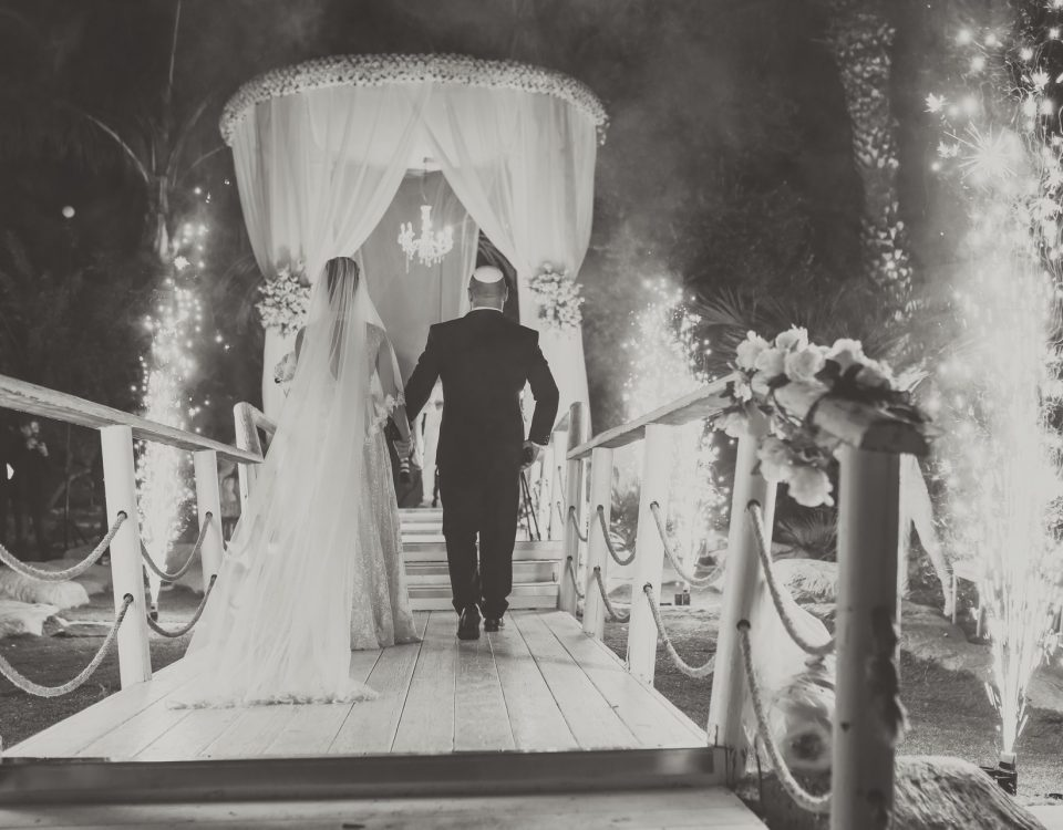bride and groom in black and white rear photo walking to the chupah