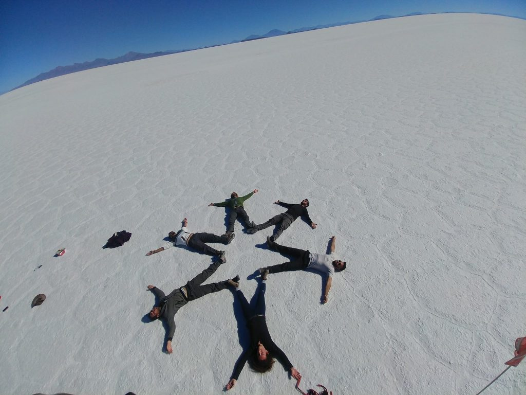 salar de uyuny or salt flats in bolivia where Israeli travelers or backpackers are laying on their backs creating a star on the ground making a cool picture