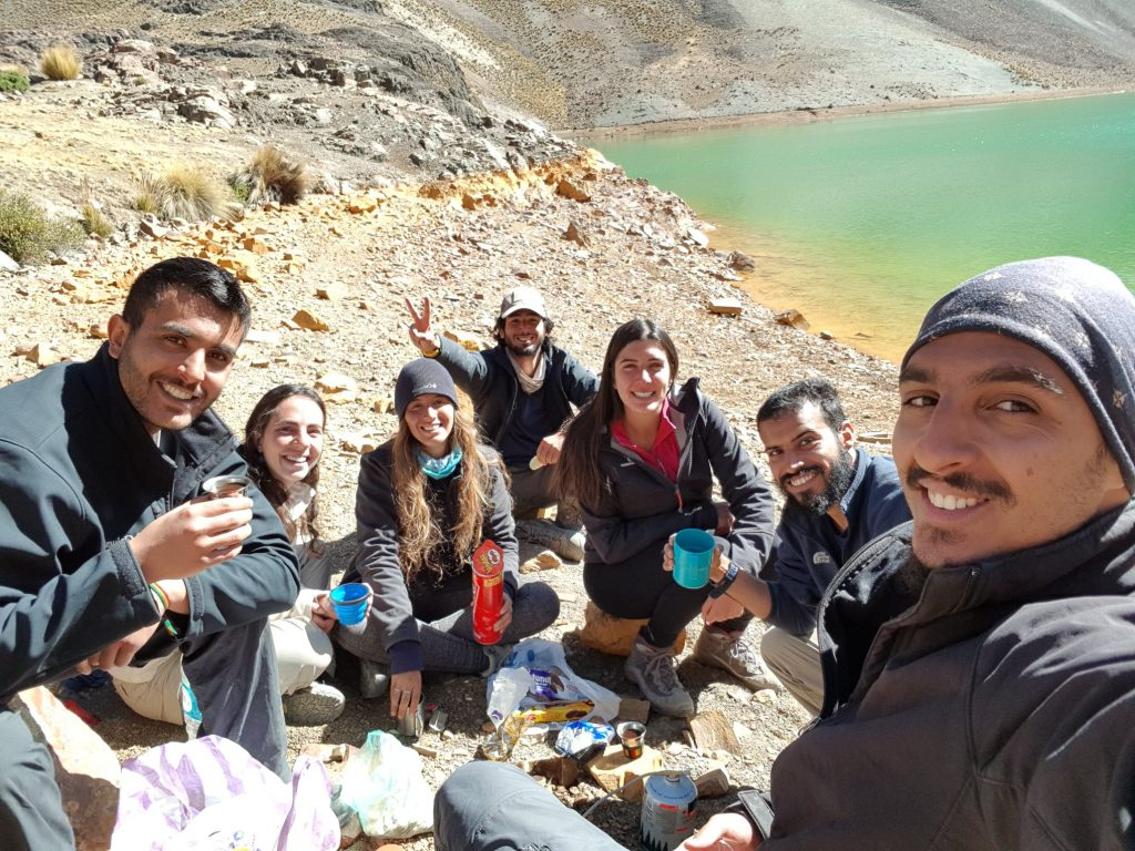 israeli backpackers sitting by a lake in south america drinking coffee and having a picknick
